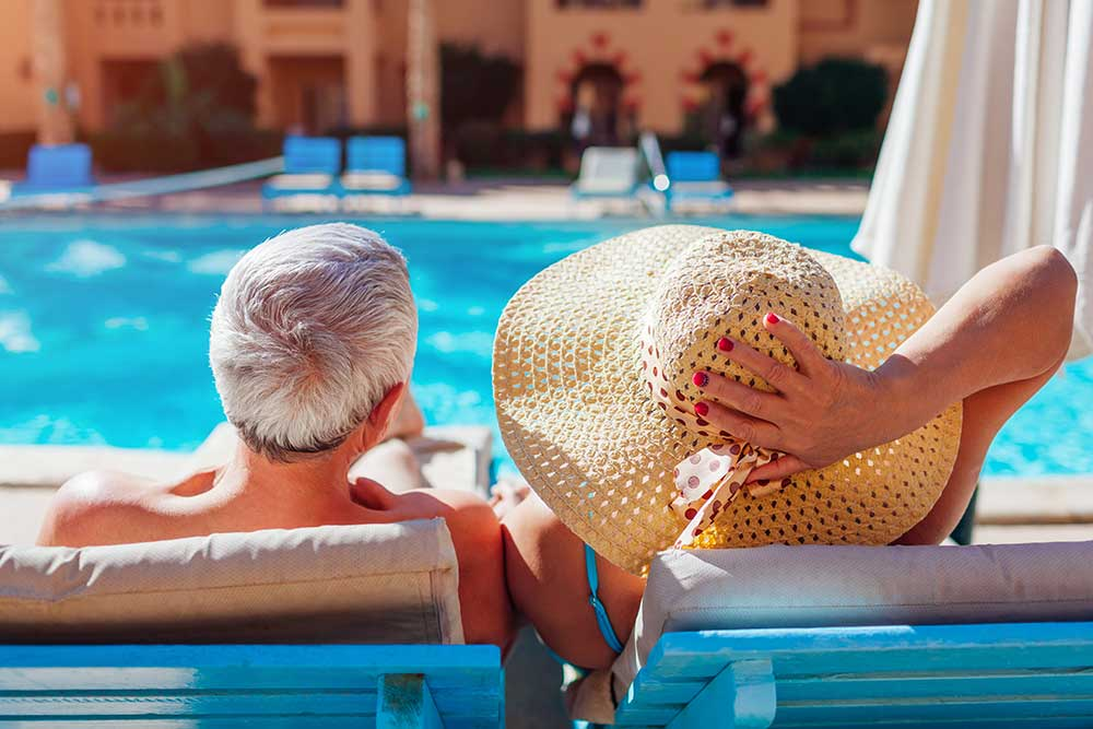 Financially successful older couple by the pool